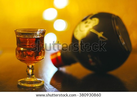 Glass of rum with soft yellow light and bokeh - stock photo