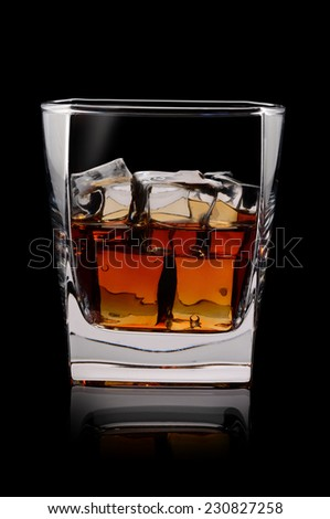 Glass of scotch whiskey and ice on a black background - stock photo