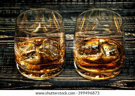Glass of scotch whiskey and ice on a black wooden background