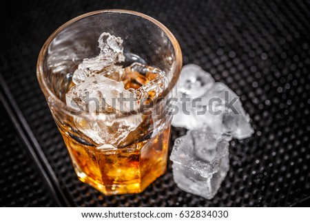Glass of scotch whiskey and ice on bar counter