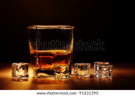 glass of scotch whiskey and ice on wooden table on brown background