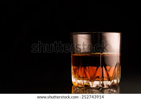 Glass of scotch whiskey on glass table - stock photo