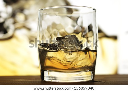 Glass of scotch whiskey on wooden table in bar