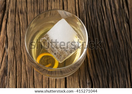 Glass of Scotch whisky on an old rustic wooden background. Modern styling with one large ice cube and orange peel as a garnish. - stock photo