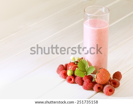 glass of smoothie on a wooden table in the garden - stock photo
