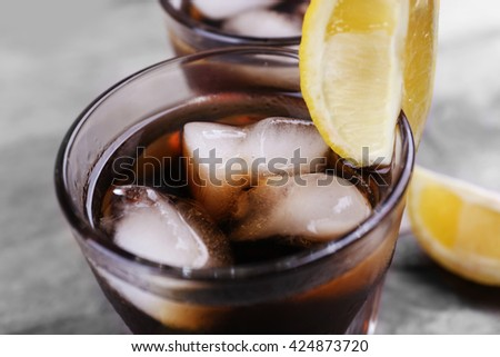 Glass of soda water with ice and lemon, close up