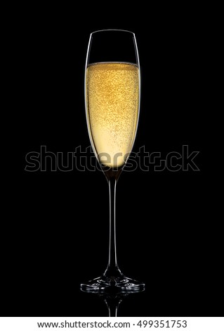 Glass of sparkling champagne with bubbles on black background