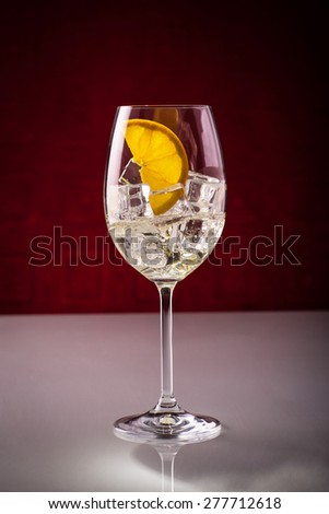 Glass of sparkling wine with ice cubes and orange slice; mixing spritz - stock photo