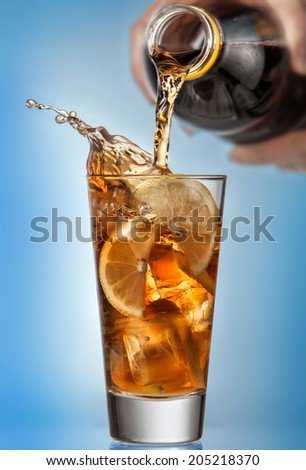 Glass of splashing iced tea with lemon and bottle on blue background - stock photo