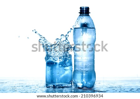 Glass of splashing water near plastic bottle. Clipping path is included - stock photo