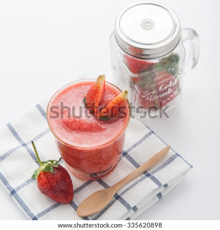 Glass of strawberry smoothie and fresh strawberries - stock photo