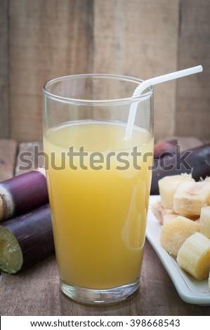 Glass of sugarcane juice on wood floor.