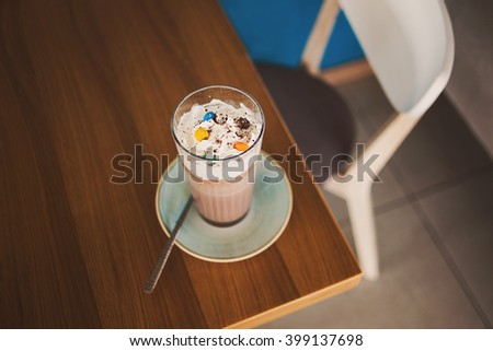 Glass of sweet cacao with chocolate and whipped cream on rustic wooden table in cafe. Top view. - stock photo