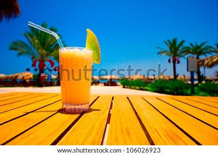 Glass of tasty juice with pipe on the table next to beach. Egypt.