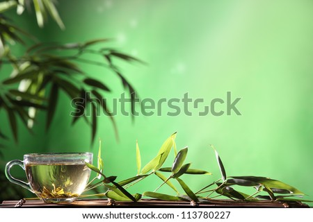 Glass of tea and bamboo leaves on table.