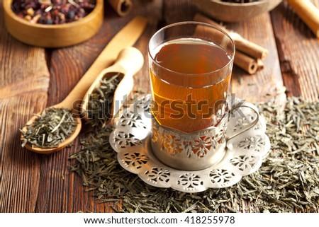 Glass of tea and dried tea leaves - stock photo