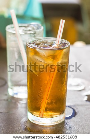 Glass of tea with ice on a table in a restaurant.
