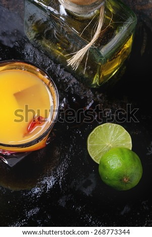 Glass of tequila sunrise cocktail, served with bottle of tequila anejo sliced limes over black background. Making tequila sunrise cocktail. - stock photo