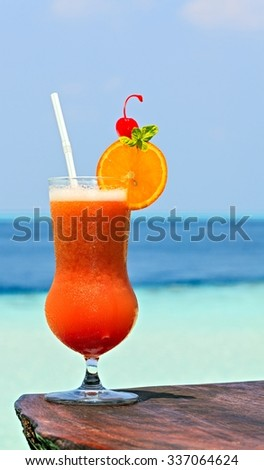 Glass of the soft drink is on a beach table (Maldives, The Indian Ocean) - stock photo