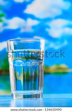 glass of the water on the beach - stock photo