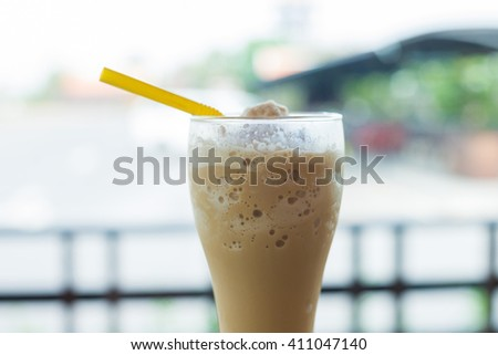 Glass of thick creamy coffee milkshake, frappe or iced coffee with a topping of ice cream and drizzled syrup - stock photo
