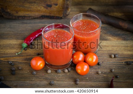 glass of tomato juice on a brown wooden background with pepper and cherry - stock photo