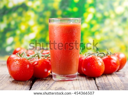 glass of tomato juice on wooden table, over green background