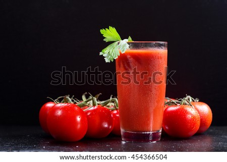 glass of tomato juice over black background