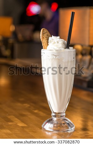 Glass of vanilla milkshake on bar counter - stock photo