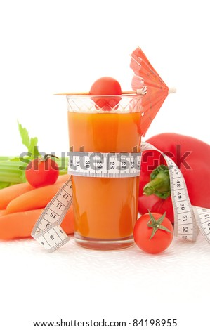Glass of vegetable juice with tape measure and fresh vegetables on white background - stock photo