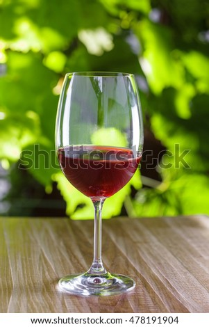 Glass of vintage red wine on a table, grapevine on background. Outdoor shot.