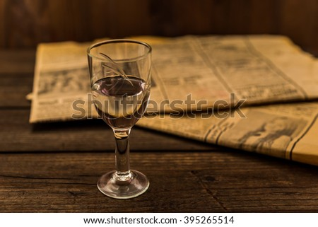 Glass of vodka and newspaper on an old wooden table. Angle view, focus on the glass of vodka