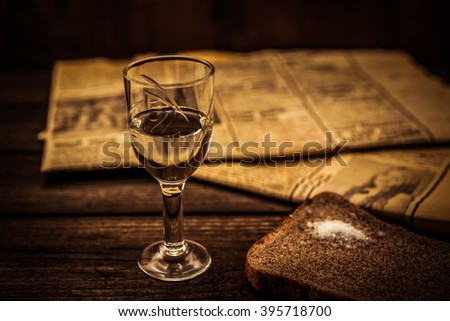 Glass of vodka and newspaper with piece of the black bread on an old wooden table. Angle view, shallow depth of field, image vignetting and yellow toning