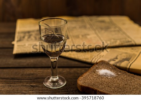 Glass of vodka and newspaper with piece of the black bread on an old wooden table. Angle view, shallow depth of field