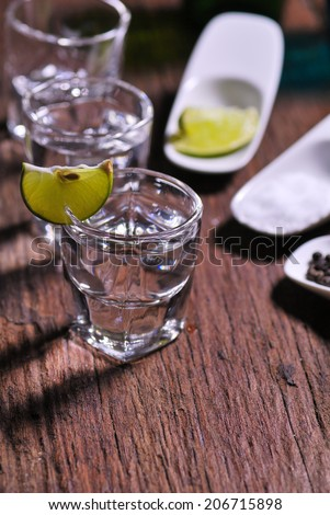 Glass of vodka shot with fresh lime on wooden table - stock photo
