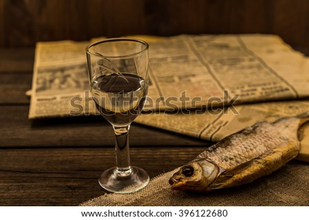 Glass of vodka with a stockfish and newspaper with canvas on an old wooden table. Angle view, shallow depth of field - stock photo