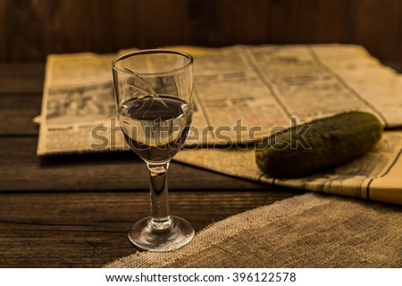 Glass of vodka with newspaper and pickled cucumber with canvas on an old wooden table. Angle view, shallow depth of field, focus on the glass of vodka