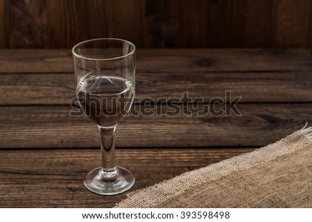 Glass of vodka with piece of cloth on an old wooden table. Angle view