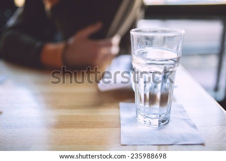 Glass of water and a man on a background