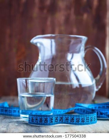 Glass of water and a measuring tape - stock photo