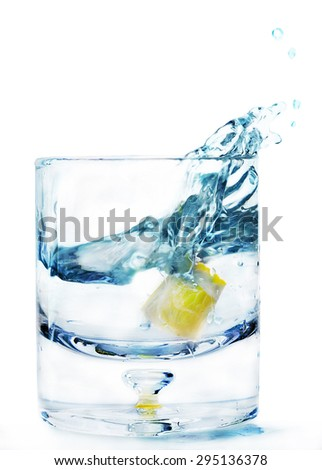 glass of water and a slice of lemon, one lemon fell in a glass, isolated on white