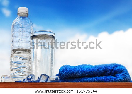 Glass of water and bottle with blue sky - stock photo