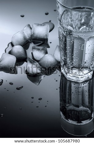 glass of water and ice cubes on a dark background of the mirror - stock photo