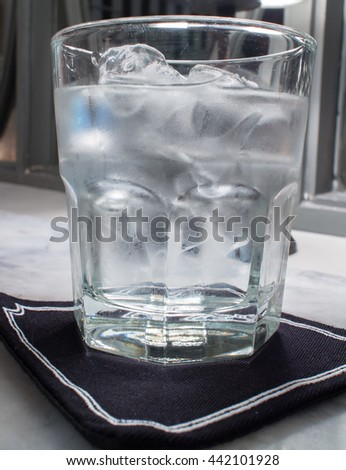 glass of water and ice in the dark room - stock photo