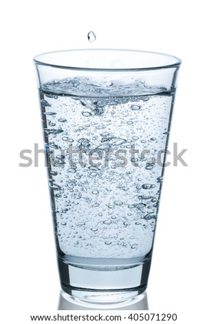 Glass of water bubbling on white background