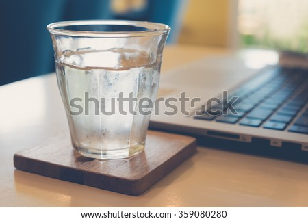 Glass of water cold on a table with laptop computer. (focus on glass) - vintage style color effect - stock photo