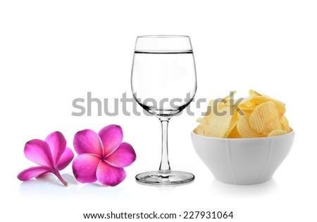 Glass of water  frangipani flower , Bowl of potato chips on white background - stock photo