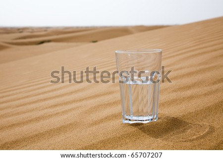 Glass of water half empty on desert - stock photo