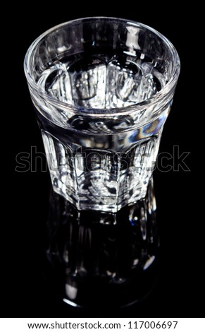 Glass of water isolated on black background with mirror reflection