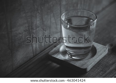 Glass of water locate on a table in food shop , Black and white picture style.